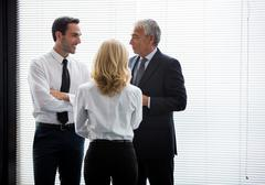 Stock Photo of Half length portrait of three businesspeople standing up and speaking