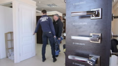 Customers looking for new internal door in the doors store showroom Stock Footage