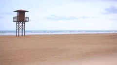 View of a sandy beach with life guard tower in Cullera background Stock Footage