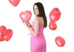 Stock Photo of Beautiful young woman with red heart balloon