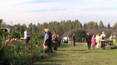 People buy plants and food sold in botanical market fair Stock Footage