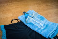 glasses and Swimming trunks , water Bottles , towel - stock photo