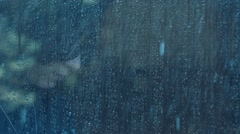 Girl behind window using smartphone in a rainy day. Shot in slowmotion Stock Footage