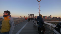 People walking on Brooklyn Bridge New York City at sunset - stock footage
