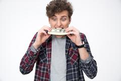 Young casual man biting money over gray background - stock photo