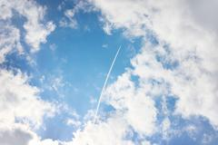 Airplane high in blue sky - stock photo