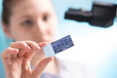 chromatogram sequencing on slide in woman hand - stock photo