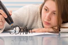 Girl uses a 3D pen to model an item Kuvituskuvat