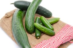 Fresh long and mini cucumbers on burlap - stock photo