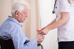 Doctor giving patient medicament - stock photo