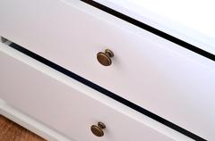 Detail of white laminated drawer with brass handle - stock photo