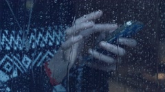 Girl behind window using smartphone in a rainy day. Shot in 4k (UHD) Stock Footage