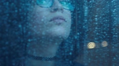 Girl behind window drinking an hot drink cup  in a rainy day. Shot in slowmotion Stock Footage