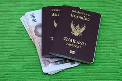 Thailand passport and Thai money - stock photo