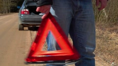 Man with warning triangle on the road - stock footage