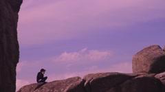 Man sitting on rock, clifftop, Dartmoor Stock Footage