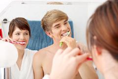 Young couple cleaning teeth. Stock Photos