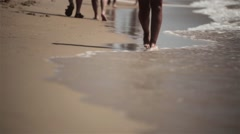 Young beautiful girl walking on the beach of the sea. Legs striding across the - stock footage