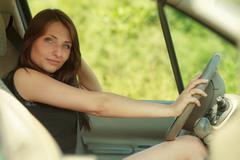 Transportation. Brunette woman driving a car Stock Photos