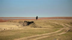 Horseman ride gallop on black horse across the field on a background of the Stock Footage