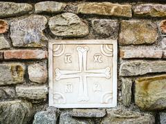 Ancient Greek Cross made of Marble on the Stone Wall Stock Photos