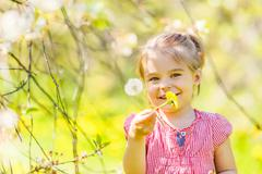 Happy little girl in spring sunny park - stock photo