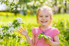 Happy little girl in spring sunny park Stock Photos