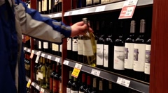 A hand takes bottles of wine from the shelf. Stock Footage
