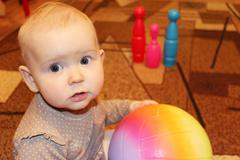 Little baby with a ball in perplexity Stock Photos