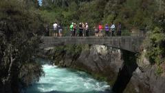 Tourists stand on bridge over Hukafalls, Taupo, New Zealand Stock Footage