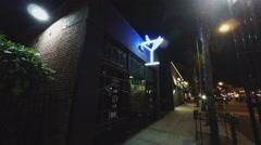 Man Exits Walks From Trendy Bar Tavern Pub- Night Stock Footage