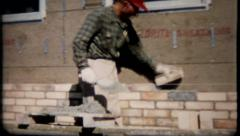 1891 - bricklayer lays brick on exterior of new home - vintage film home movie Stock Footage