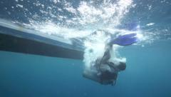 Female scuba diver backward roll entry from boat into ocean Stock Footage