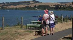 Two women walk the dog along banks of Lake Taupo, New Zealand Stock Footage
