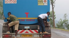 African children sneaking a ride on back of big blue truck Stock Footage