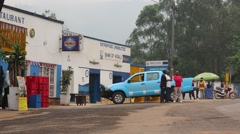 Pedestrians Stand at a Way Stop Along a Rwandan Main Road - stock footage