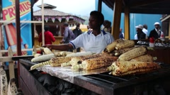 African woman selling roasted corn on grill Stock Footage