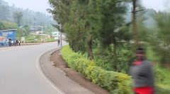 Passing Shot of Man on Bicycle Pedaling Down an African Road - stock footage