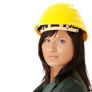 Young female architect or builder wearing a yellow hart hat - stock photo