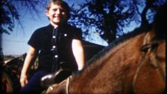 1900 - young farm girl rides a horse around barnyard - vintage film home movie Stock Footage