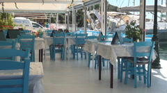 Restaurant with tables and chairs in a Mediterranean port, Summer day, Vacation. - stock footage