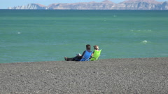 Two people sit on the beach near the Marine Parade, Napier, New Zealand Stock Footage
