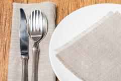 Empty white plate spoon, fork, knife - stock photo