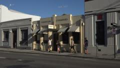 People walk past Art Deco buildings on Tennyson Street, Napier, New Zealand Stock Footage