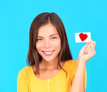Smiling young teen girl holding card sign in hand - stock photo