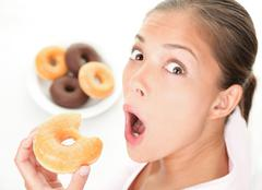 Funny woman eating junk food Stock Photos