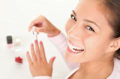 Putting nail polish - beauty fun woman - stock photo