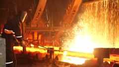 Male worker cuts fiery steel blocks at the factory Stock Footage