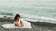 Pretty Woman Relaxing on Beach At Dull Day - stock footage