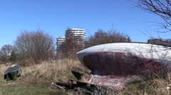 Boat wreck in front of newly built residential building Stock Footage
